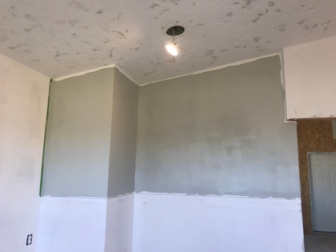 Room with level five mudded walls and textured ceiling with a line diving the top half and bottom half of the wall, and the top half has been painted with green gray paint