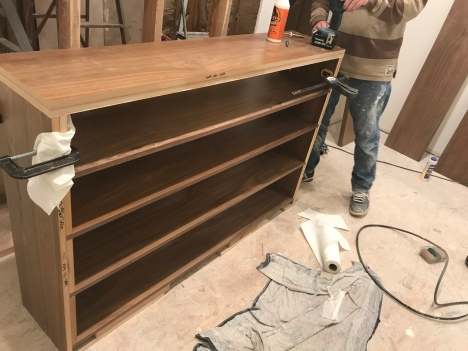 Walnut shoe shelf in the process of being built in an unfinished room