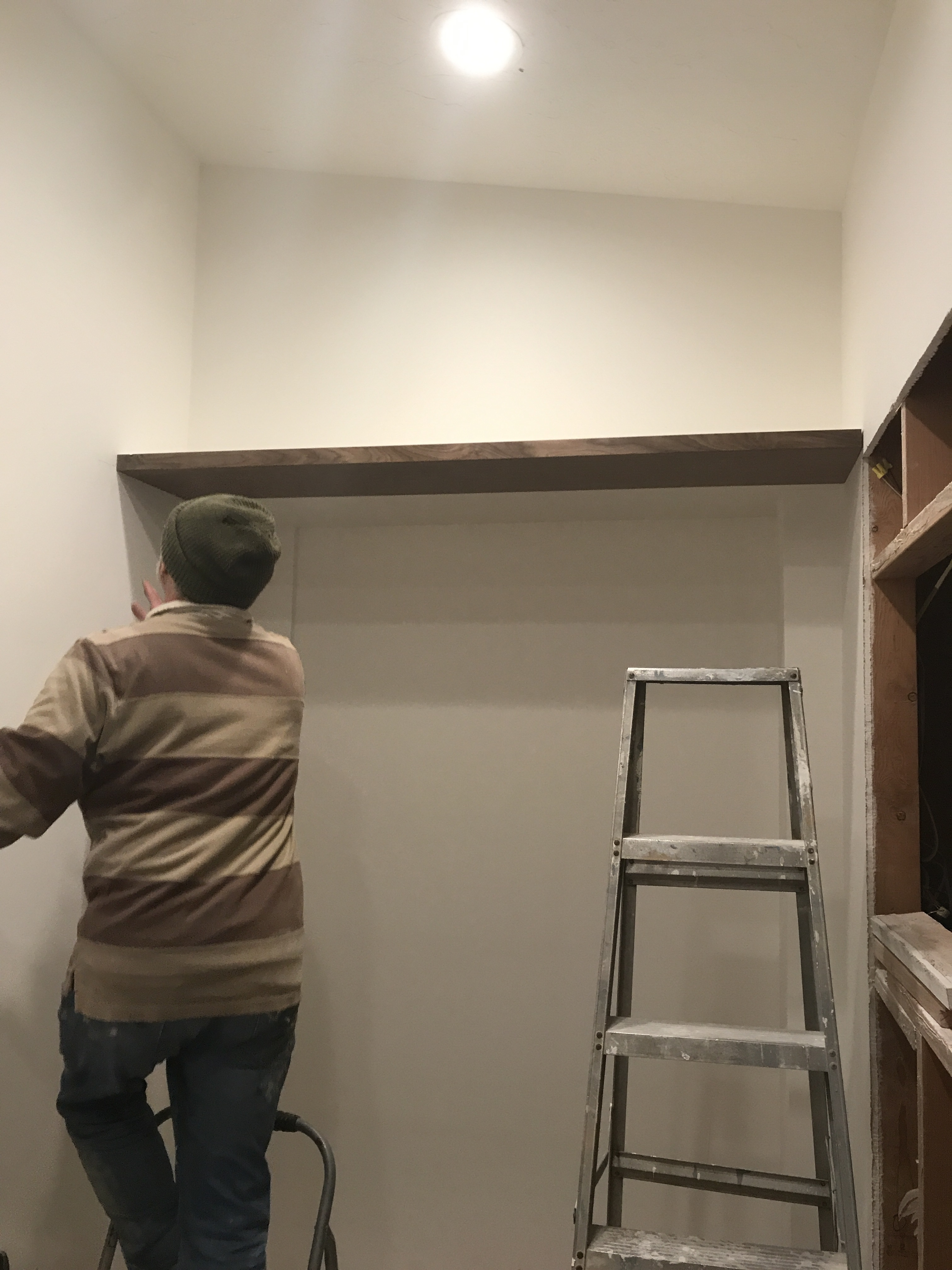 A floating walnut shelf in a white room with a man inspecting it, and an old ladder to the right.