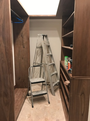 Walnut closet built in shelves in a room with unfinished floors and two ladders.