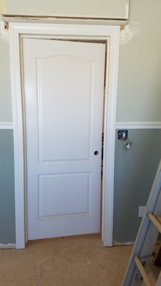 A white solid wood door with a fresh coat of paint hung in a door frame in a room with two tone green and gray paint with a chair rail and molding around the door. No door knob installed