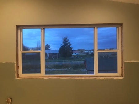 a large unframed window set in a wall with the top half painted in a green gray paint, and the bottom half is painted in a dark green gray paint.