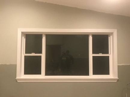 a large white framed window set in a wall with the top half painted in a green gray paint, and the bottom half is painted in a dark green gray paint.
