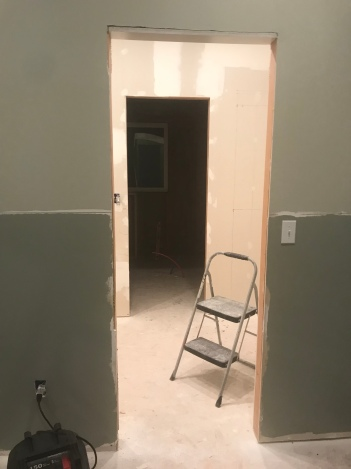 An unfinished doorway set in a wall with the top half painted in a green gray paint, and the bottom half is painted in a dark green gray paint.  There is an unfinished room in the background