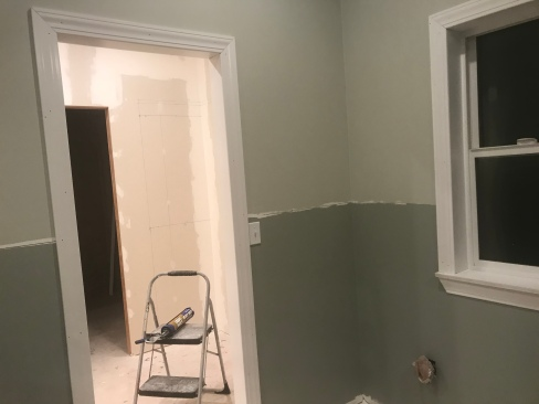 a corner on a wall with the top half painted in a green gray paint, and the bottom half is painted in a dark green gray paint with a white framed door way too the left and a white framed window to the right.  There is an unfinished room through the doorway in the background