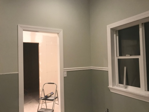 a corner on a wall with a chair rail dividing the top half that is painted in a green gray paint, and the bottom half is painted in a dark green gray paint with a white framed door way too the left and a white framed window to the right.  There is an unfinished room through the doorway in the background