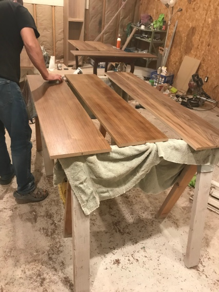Panels of walnut sitting on sawhorses in a workshop and a man inspecting them