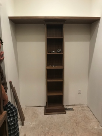 A walnut built in tall skinny shelf with a floating shelf above it in a room with unfinished floors.