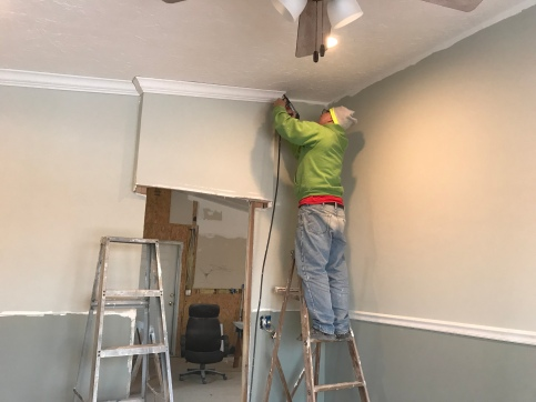 A man on a ladder with a pin nail gun installing white crown molding in a room a with a chair rail dividing the top half that is painted in a green gray paint, and the bottom half is painted in a dark green gray paint with an unframed door way too the left. There is an unfinished room through the doorway in the background