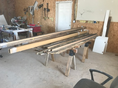 A pile of wood of various sizes sitting on a pair of saw horses in a wood shop