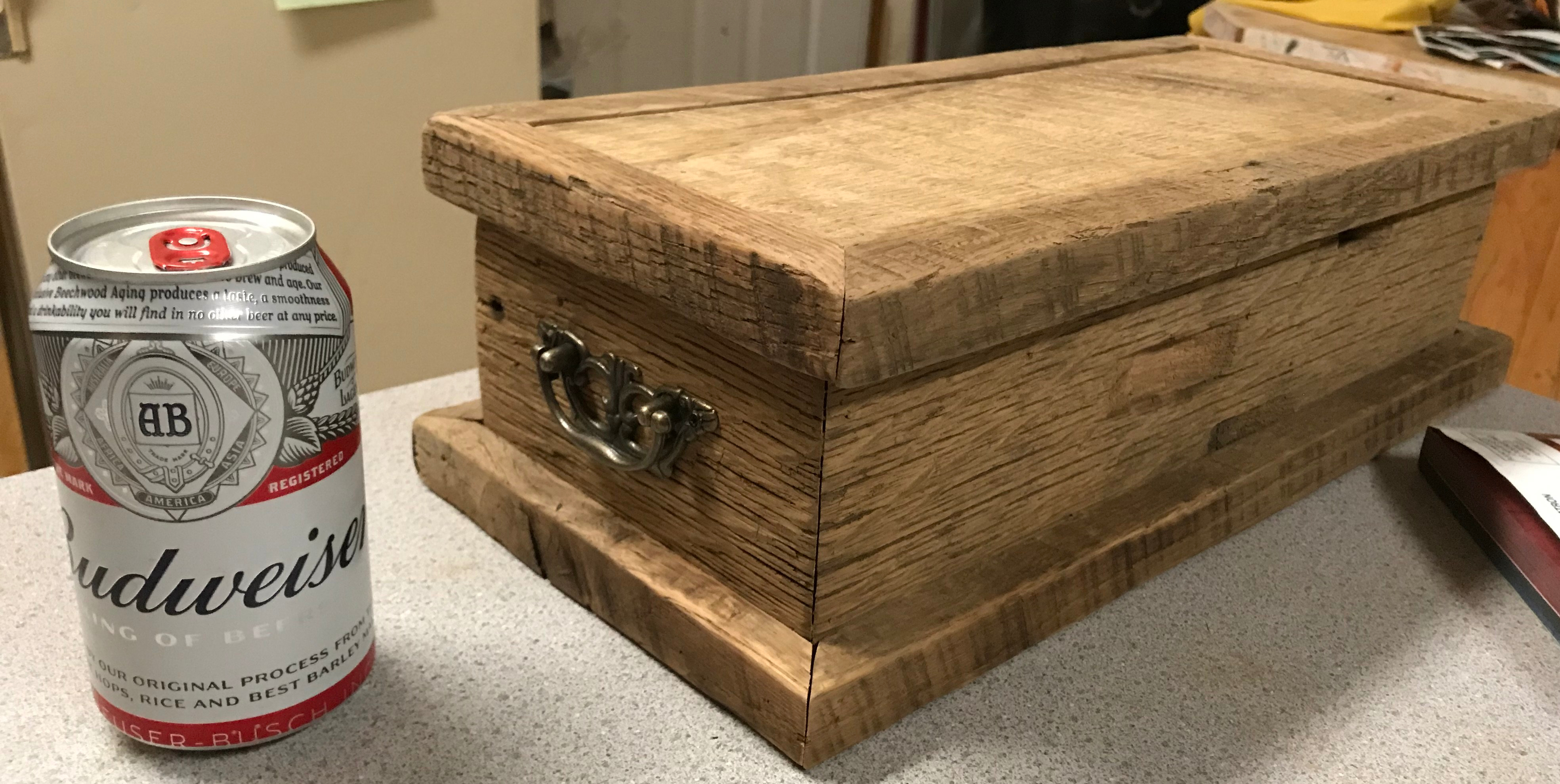 An oak wood box with brass hanging handles sitting next to a can of Budweiser