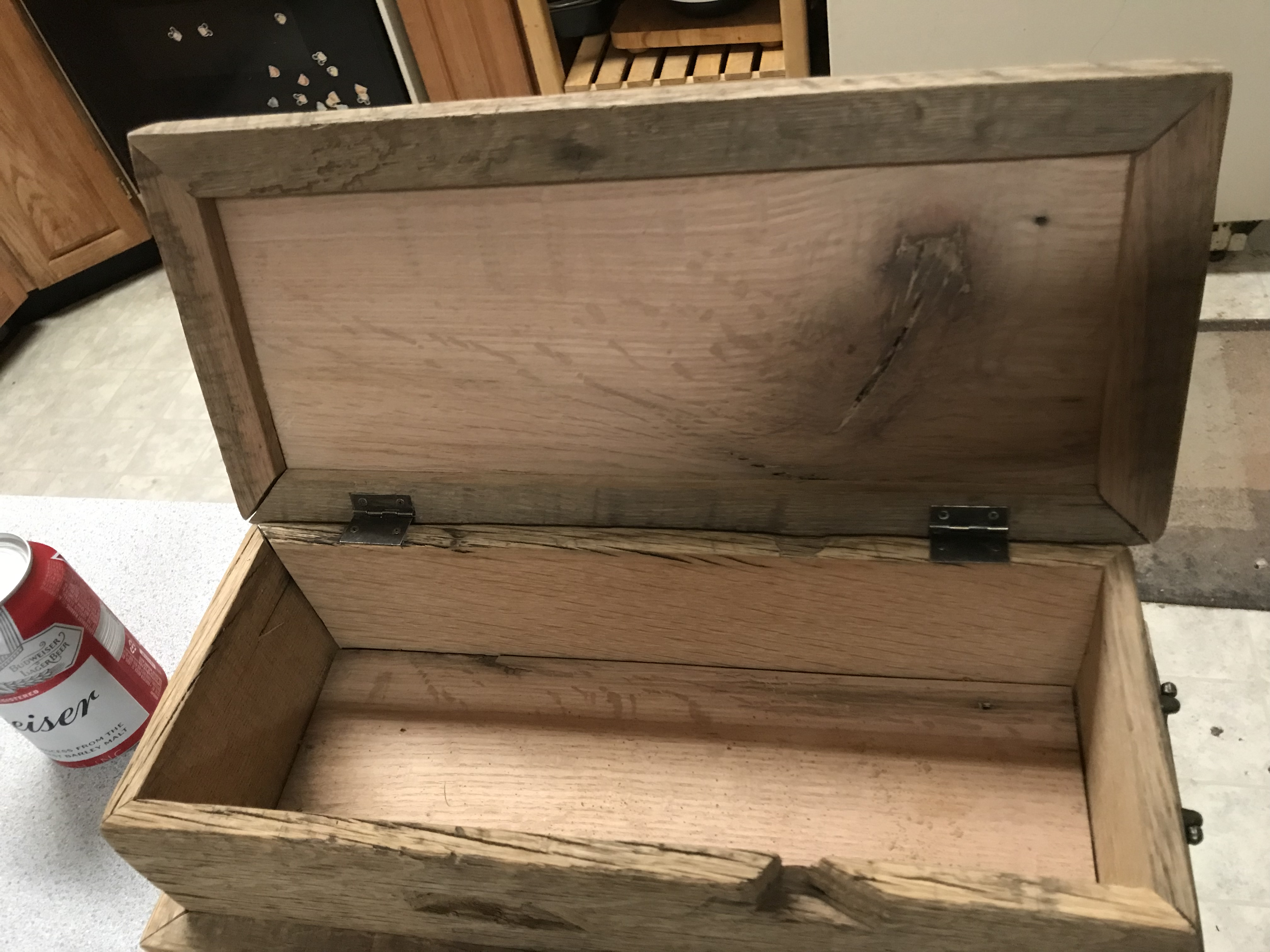 The inside of an oak wood box with the top opened on hinges