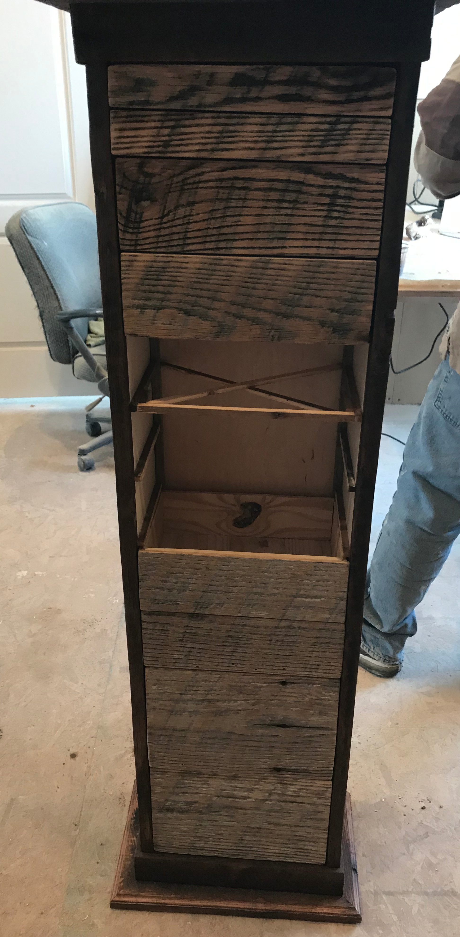 Tall skinny apothecary cabinet with the top four drawer fronts after being waxed, the next three are missing, and the next four drawers are not waxed