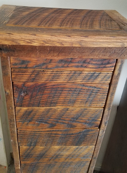 The top half of a tall skinny apothecary cabinet with sequenced oak saw tooth marked drawer fronts that have been coated with beeswax