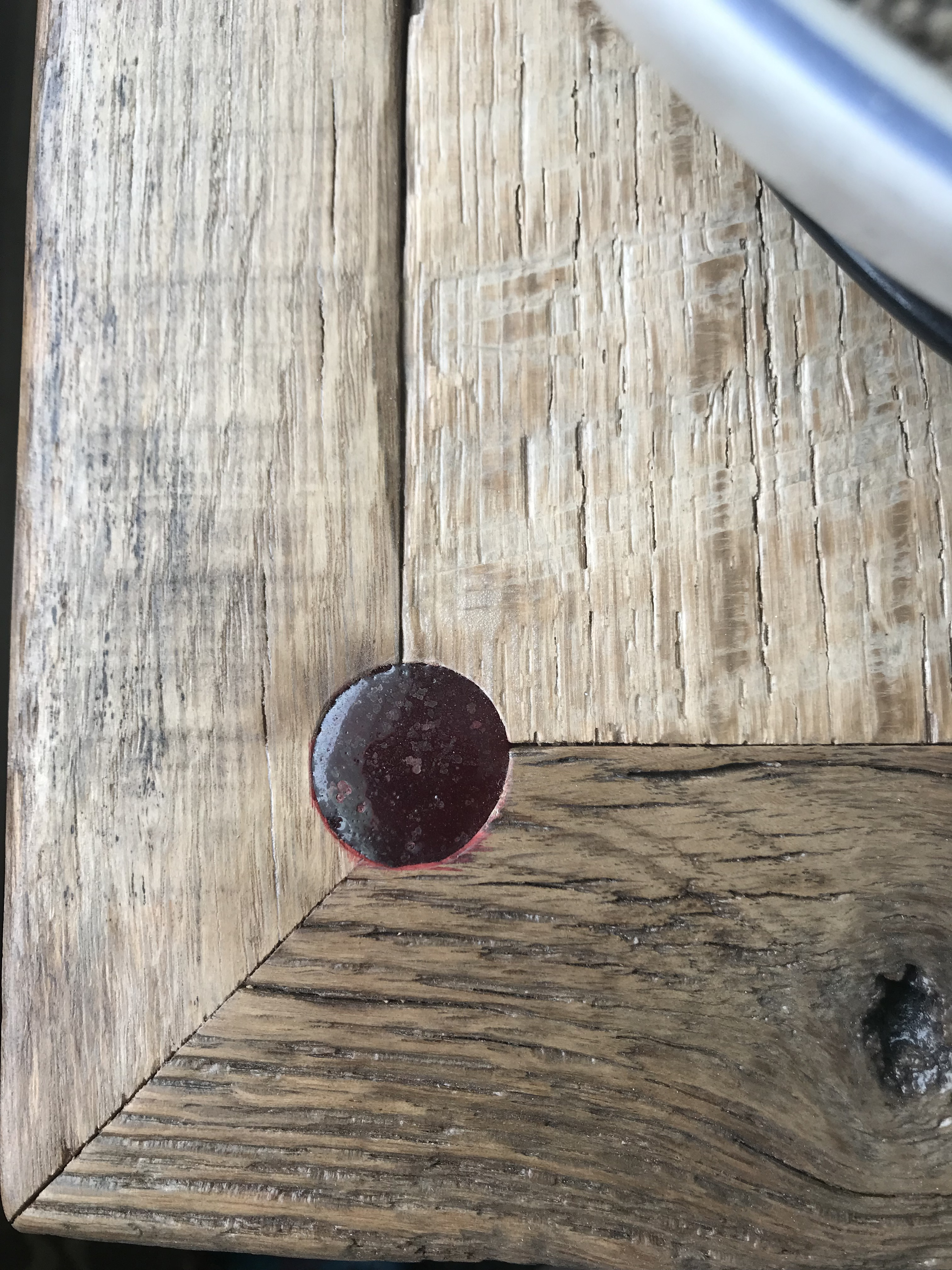 A close up look at the corner of an oak barn wood bench corner with a circle in the corner of the panel that meets the edges of two mitre frame pieces filled with red epoxy