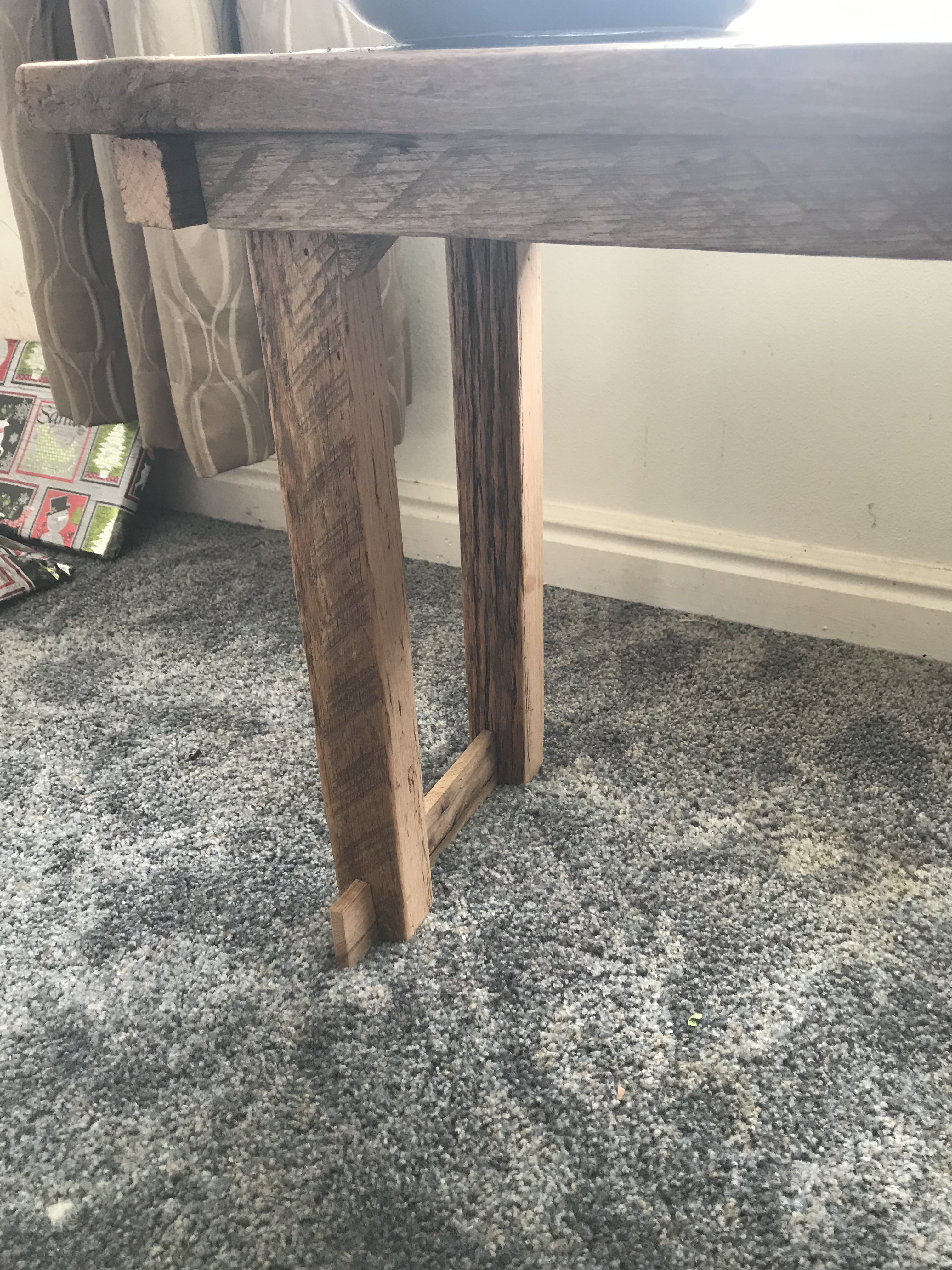 An oak barn wood bench with oak saw tooth marked skirt and legs sitting in front of a window on blue carpet