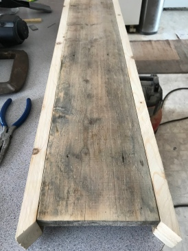 Reclaimed wood plank with nail holes and two mitered 2x3s on the sides for molding