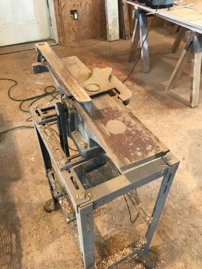 Old jointer used in woodworking sitting in a work shop with saw dust and wood chips dusted on it