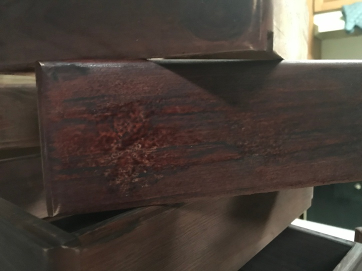 close up image of a drawer box fram sprayed with minwax polyshades bombay mahogany that shows messy spray marks