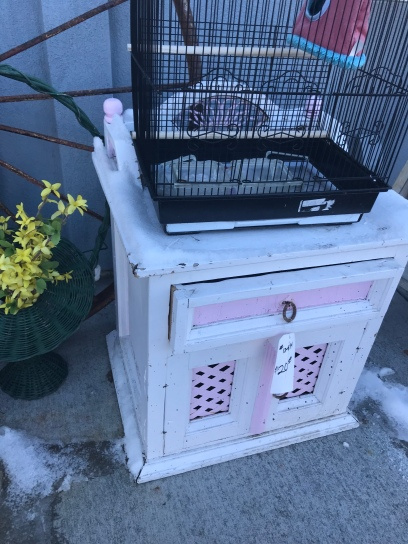 A white and pink side table sitting on a sidewalk covered in snow with a bird cage and other random junk around it