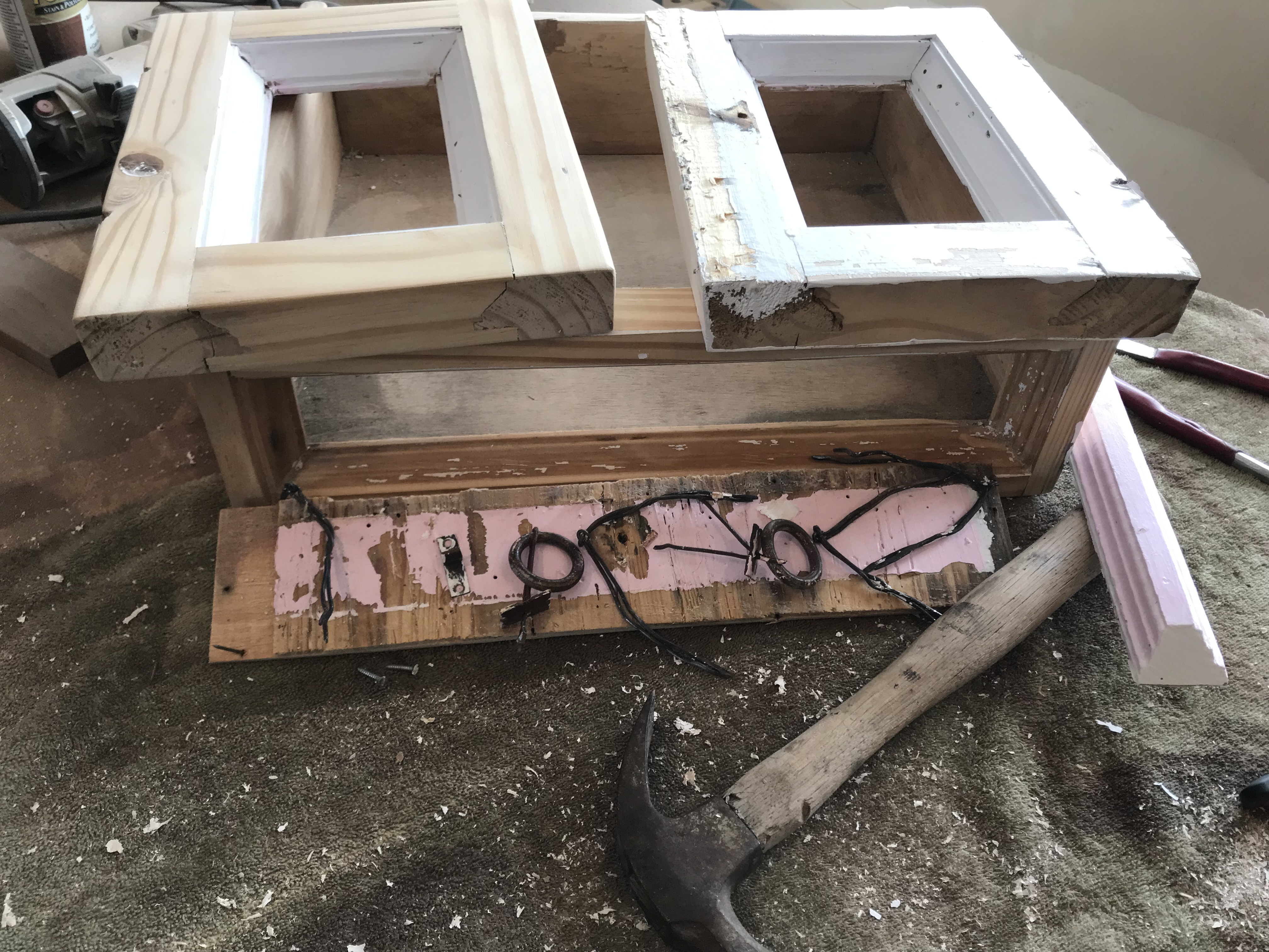 A thin wide cabinet drawer with two small cabinet doors sitting on top of it in various stages of paint scraping and sanding, and a pink drawer face with old wire hinges and drawer pulls sitting in the foreground