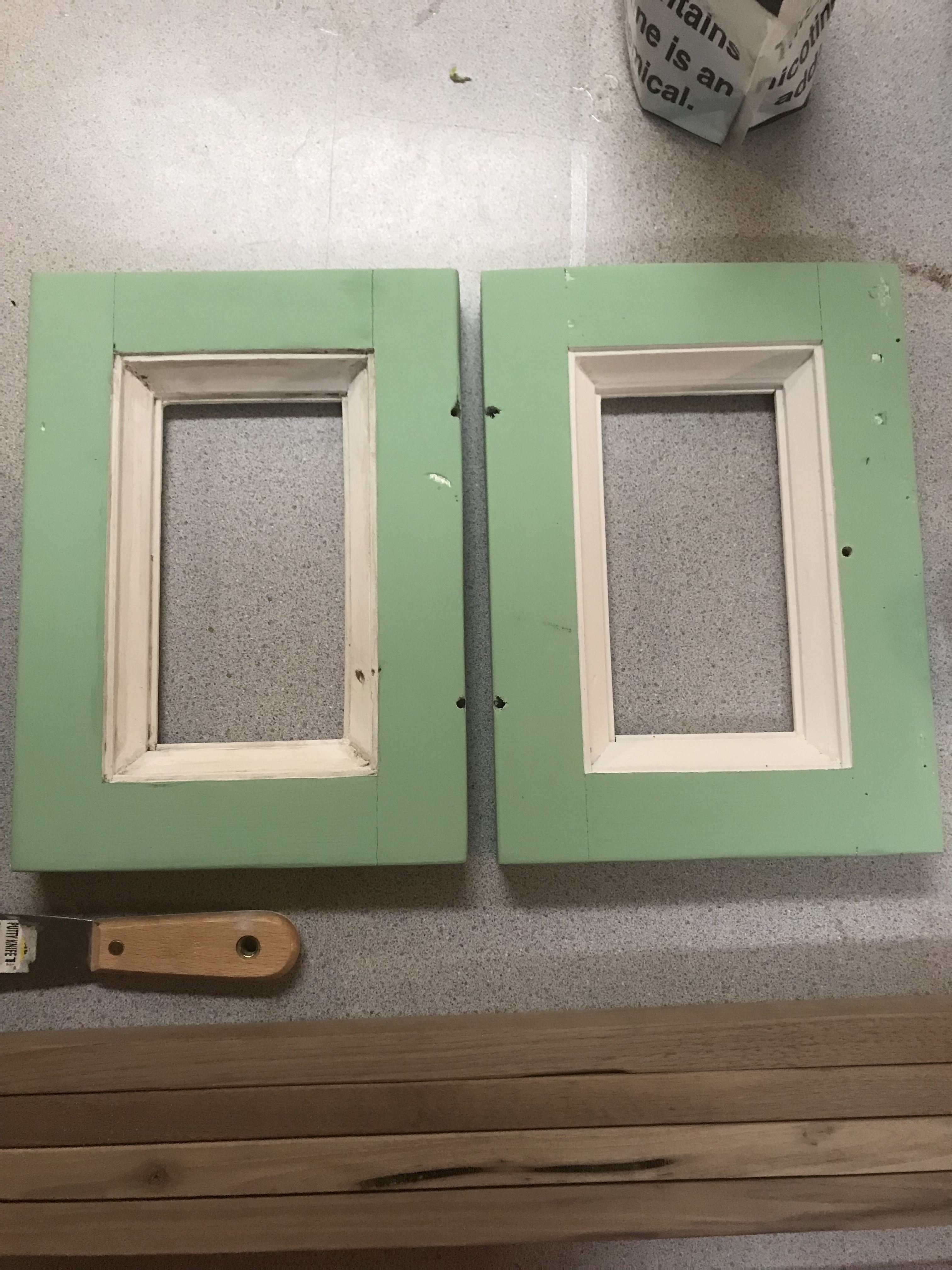 Two small cabinet doors with white inside molding and mint green panels with a drywall spatula in the foreground