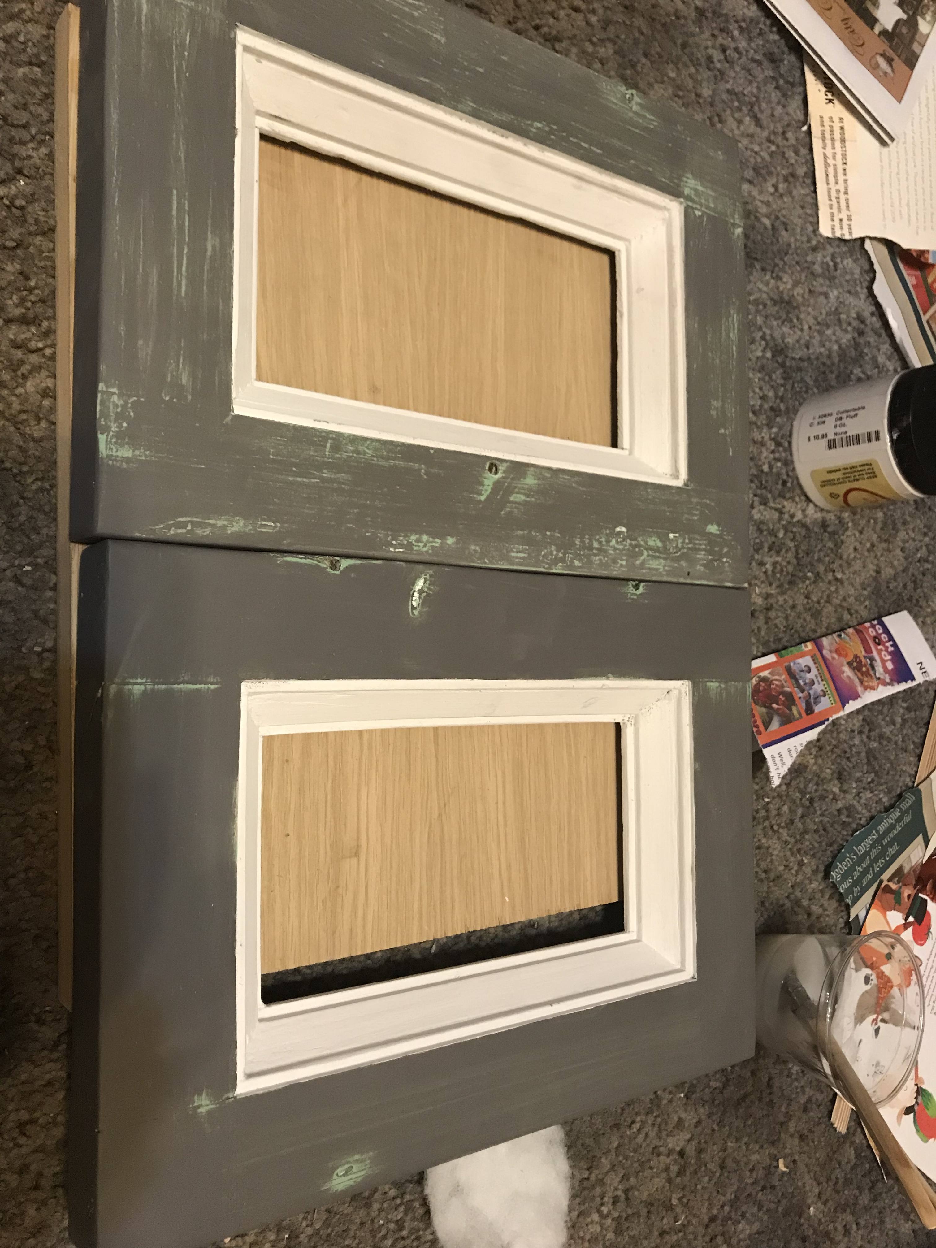 Two small dresser doors with white molding and gray panels with a mint green colored distressed through the gray paint
