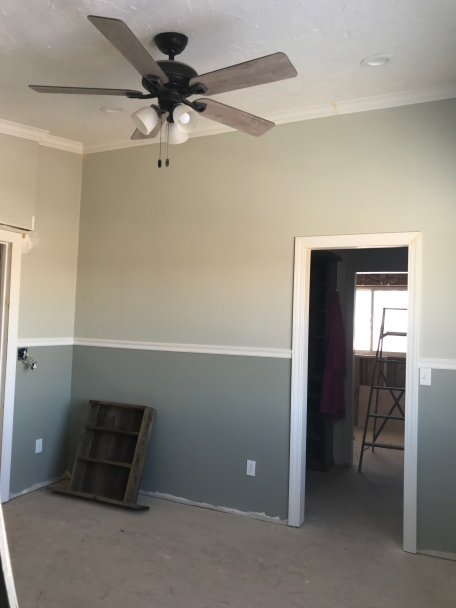 A finished room with a white textured ceiling with can lights and a black fan with tan wood colored arms and 3 lights.   The room has white crown molding in a room a with a chair rail dividing the top half that is painted in a green gray paint, and the bottom half is painted in a dark green gray paint with a framed door way to the left and right. There is an unfinished room through the doorway in the background.  The floor is raw plywood.