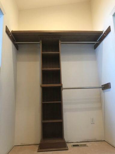 A walnut built in tall skinny shelf with a floating shelf above it with two clothes rods on the right, and one clothes rod on the left with clothes hooks next to the upper rods on the left and right sides in a room with unfinished floors.