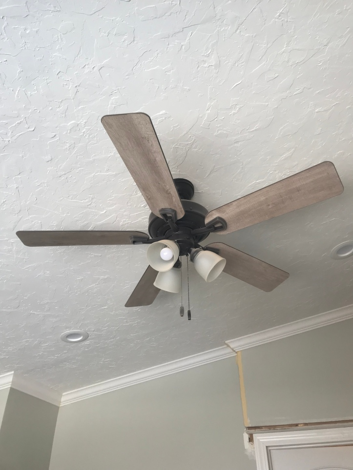 A black ceiling fan with tan wood colored arms and three lights in a room with a white textured ceiling and can lights with white crown molding and a chair rail dividing the top half that is painted in a green gray paint, and the bottom half is painted in a dark green gray paint.