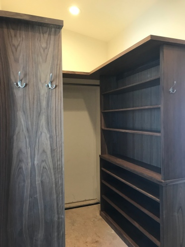 Walnut built in shoe shelf with hard wood nosing and a larger upper shelf with clothes hooks on the ends of the shelf.