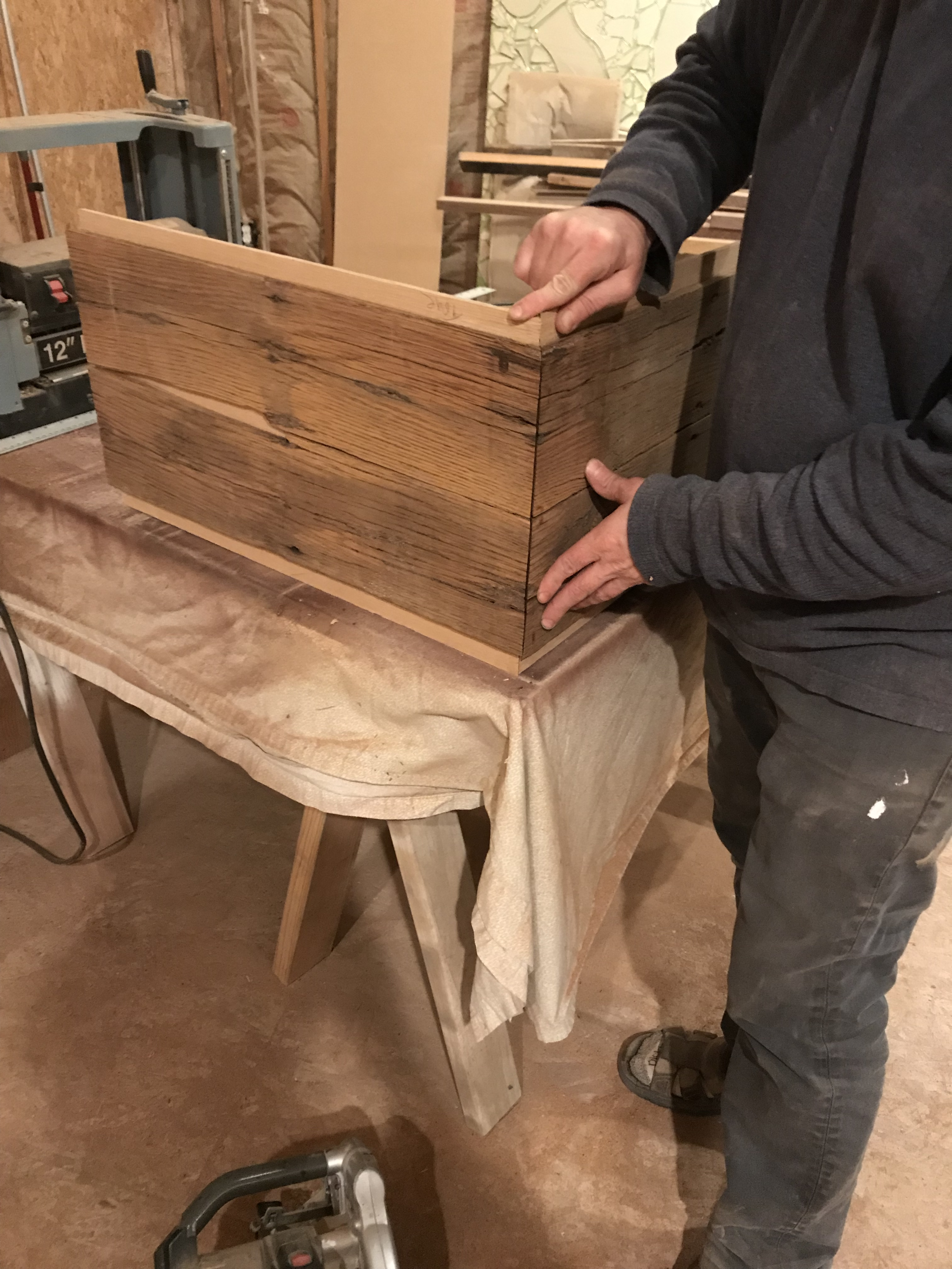 Reclaimed oak barn wood layed up on quarter inch material and miter cut for a continuous waterfall edge, sitting on a table in a work shop with a man holding the edges together.