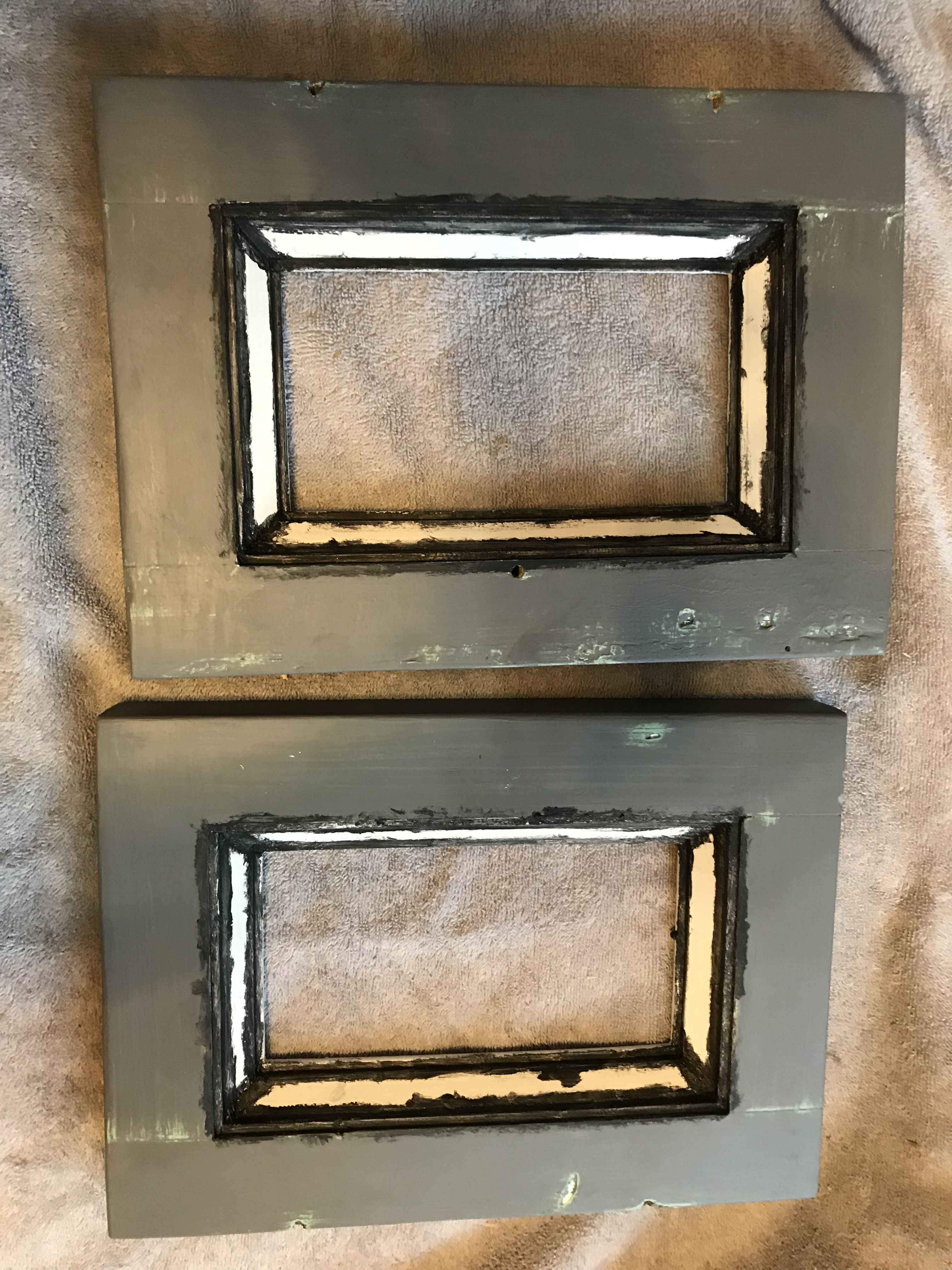 Two small dresser doors with white molding that has black wax painted on it and gray panels with a mint green colored distressed through the gray paint