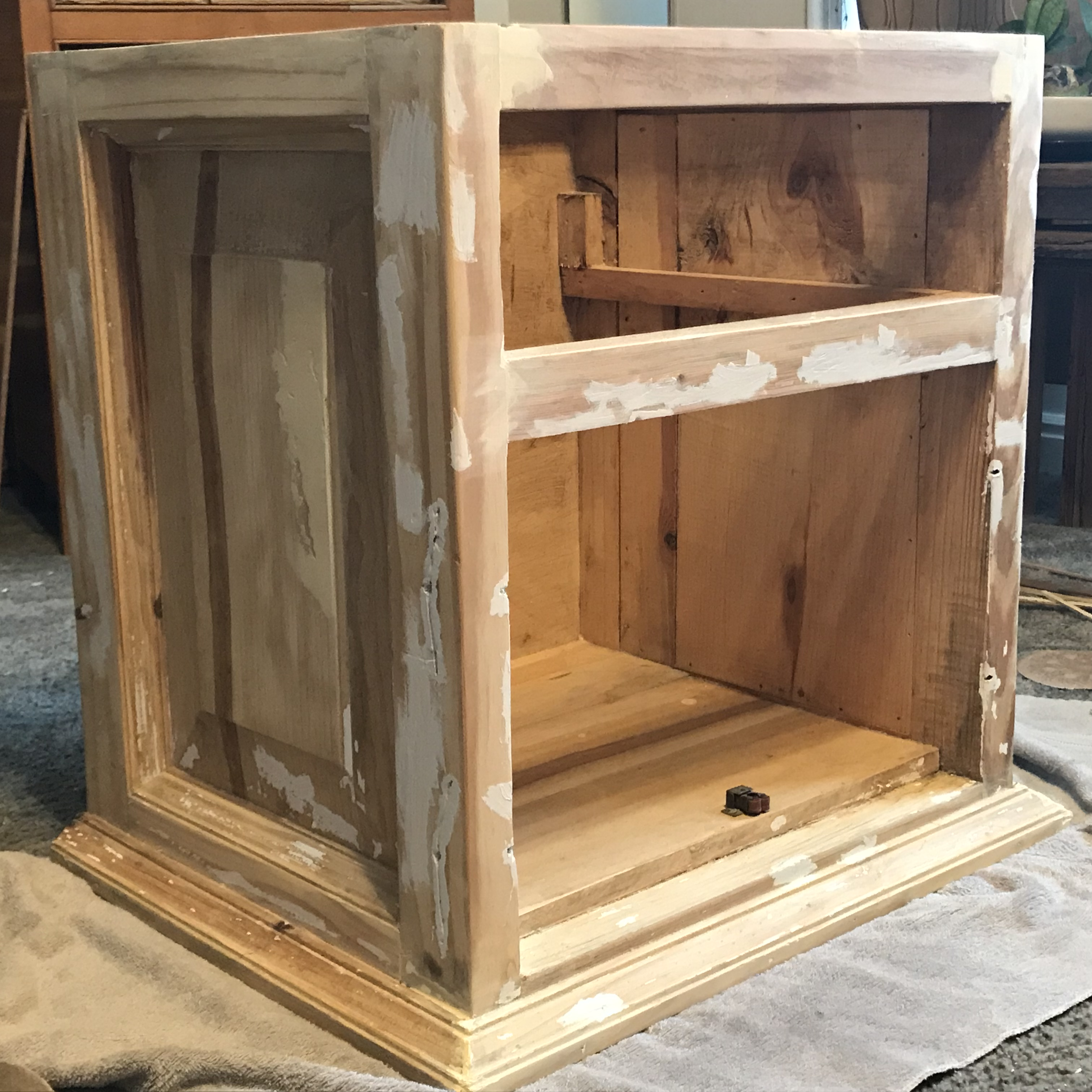 A raw wood cabinet with white paint scraped off with missing doors and drawer