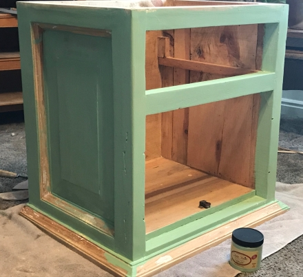 A painted mint green cabinet with missing doors and drawer