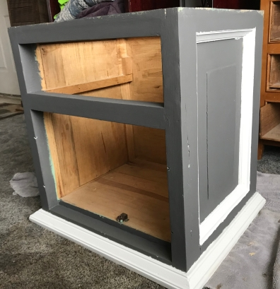 A gray painted cabinet with white molding and missing doors and drawer