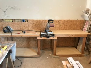 Two tables made of 2x4's and melamine tips with melamine shelves underneath on either side of a miter saw on a stand.