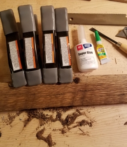 Reclaimed oak wood board with clamps on it and super glue in the background