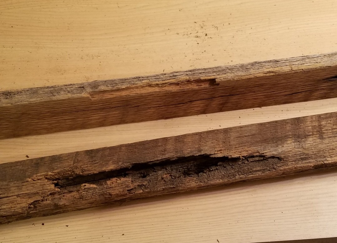 Two oak wood boards with the top one that has the chip out and the bottom one is rotted out