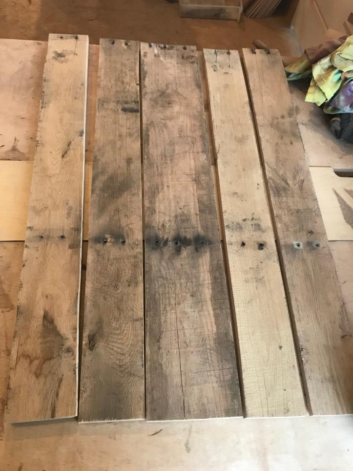 Reclaimed oak pallet wood sitting on a table in a workshop.