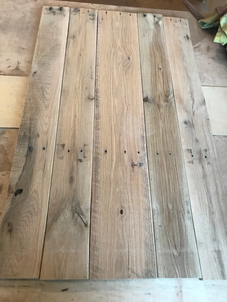 Reclaimed oak pallet wood after sanding and planing sitting on a table in a work shop.