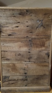 Drawer fronts on a medcentury style cabinet that have been sequenced from reclaimed oak barn wood with old nail holes, saw tooth marks and knots.