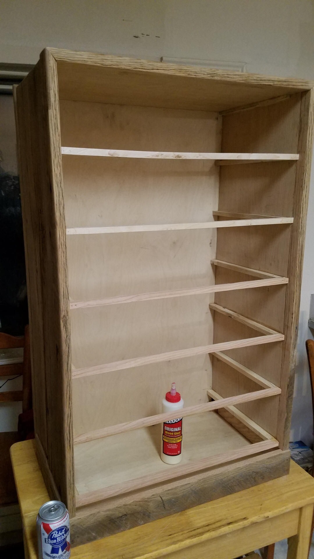 The frame of a midcentury modern oak barn wood cabinet with drawer rails installed