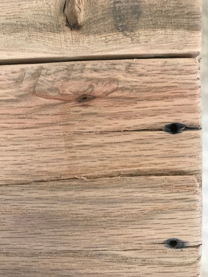 Close up view of a piece of oak that has a crack in it, and old blackened nail holes