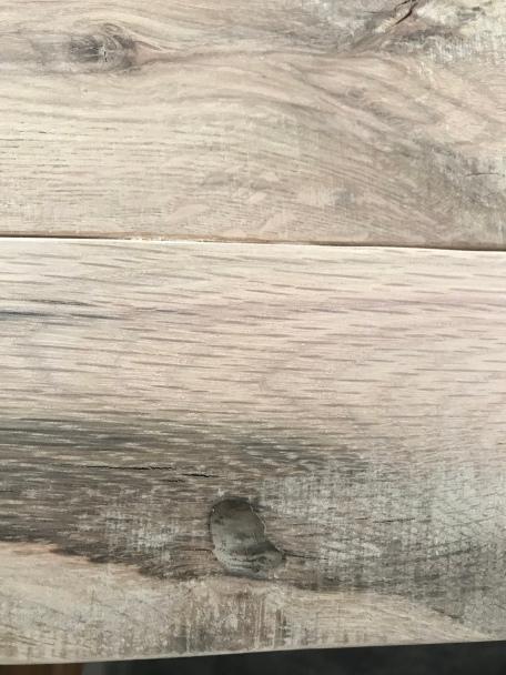 An oak wood board with a deep knot in it
