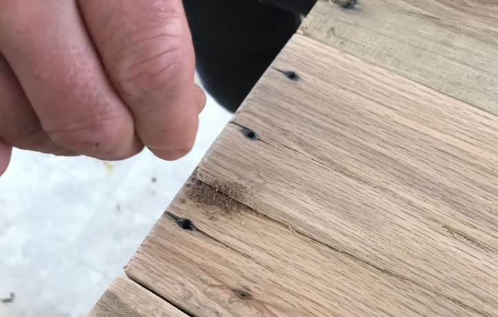 A hand sprinkling walnut dust on a piece of oak that has a crack in it, and old blackened nail holes