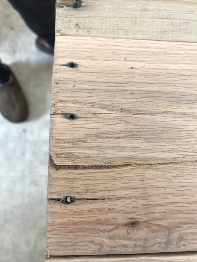 An oak board with a crack in it that has been filled with walnut dust