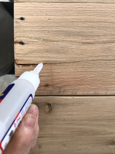 An oak board with a crack in it that has been filled with walnut dust and super glued