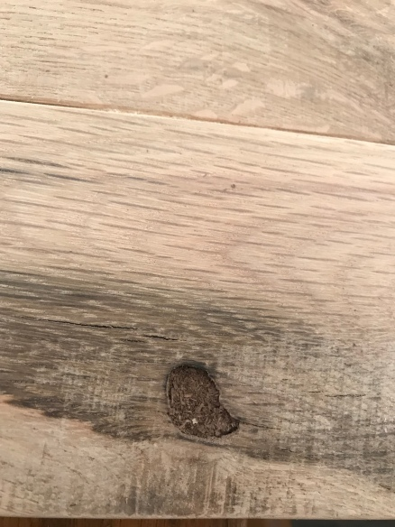 An oak wood board with a knot in it filled with walnut wood dust