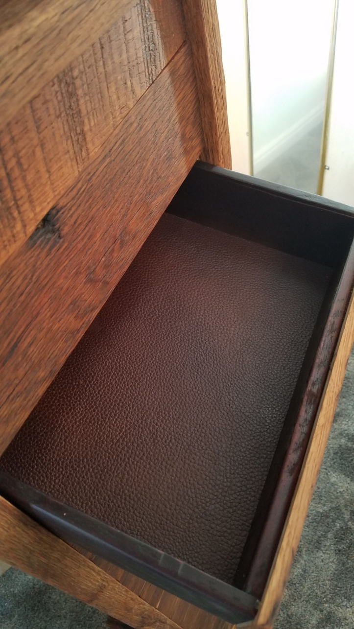 A close up view of a cabinet with one open drawer that has brown leather in the bottom of the drawer